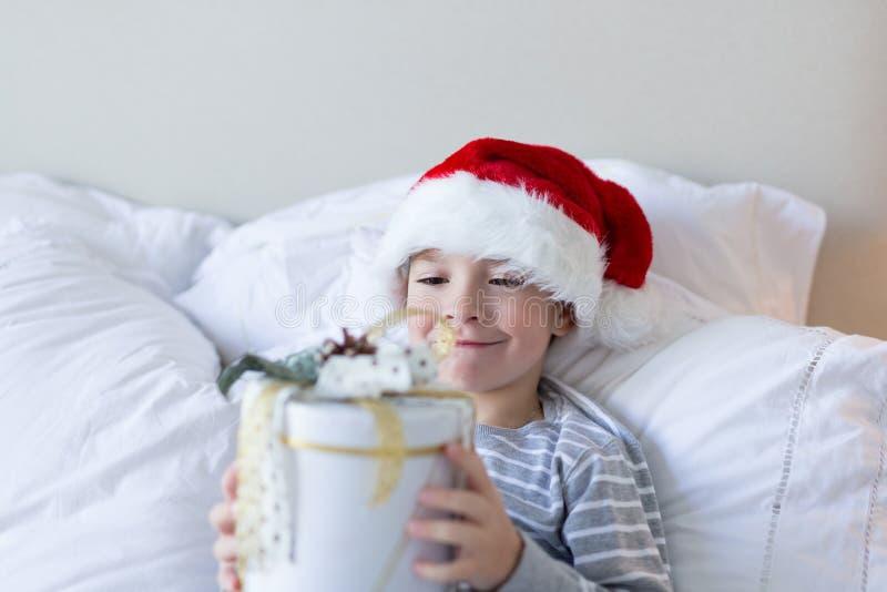 lyckligt nytt xmas-år Den lyckliga le pojken i röd hatt för jultomten sitter i säng som rymmer den närvarande asken inomhus Jul o royaltyfri foto