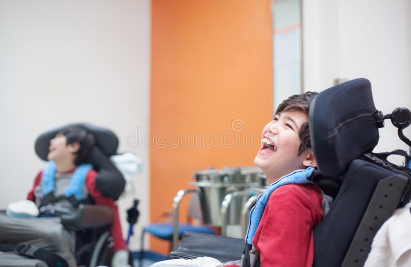 Lyckligt och att le den rörelsehindrade pojken i rullstolen som väntar i doktor av royaltyfria foton