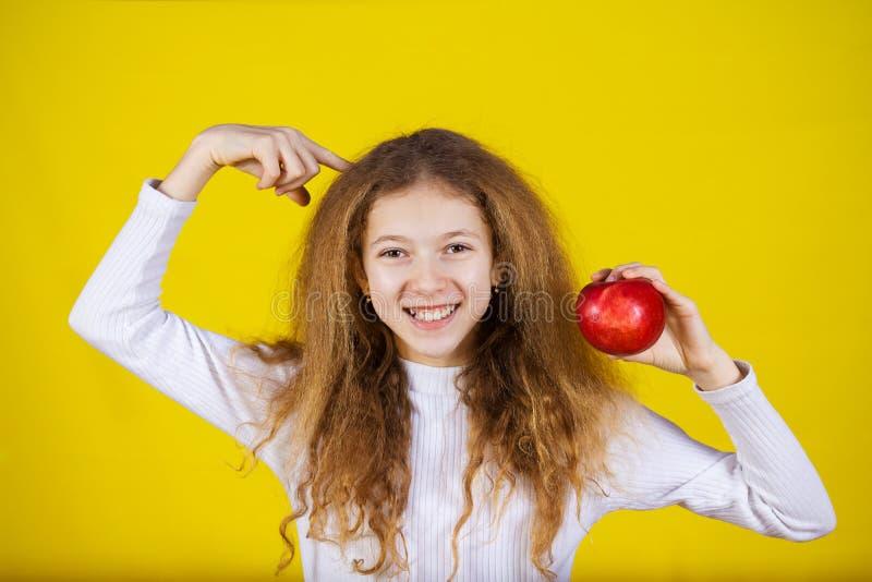 Lyckligt och att le lilla flickan som rymmer ett rött äpple royaltyfri bild
