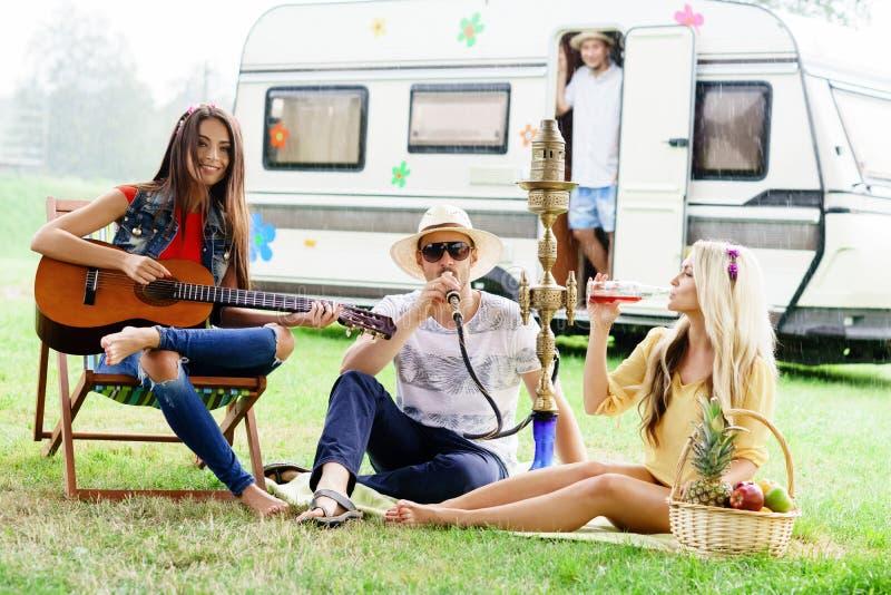 Lyckligt och att le vänner som har en picknick utomhus royaltyfria foton