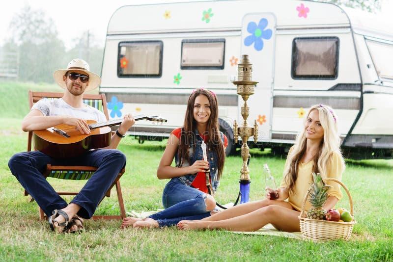 Lyckligt och att le vänner som har en picknick utomhus fotografering för bildbyråer