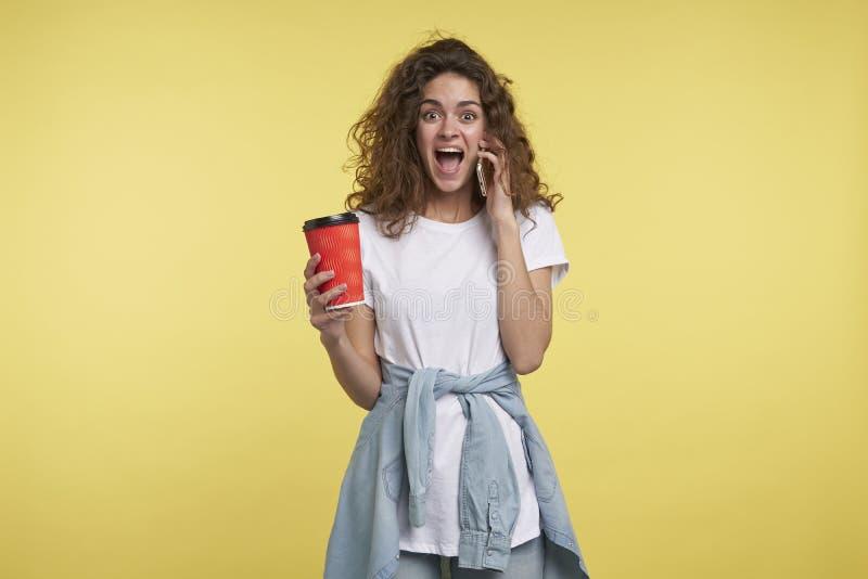 Lyckligt och förvånat av påringningbrunettkvinnan med lockigt, innehav ett hår för kaffekopp, studioskott som isoleras över gulin arkivfoton