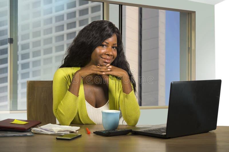 Lyckligt och härligt svart arbeta för afrikansk amerikanaffärskvinna som är säkert på att le för datorskrivbord som tillfredsstäl arkivfoto