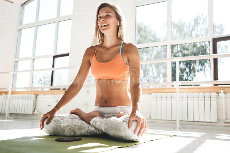 Lyckligt och le bärande sportwear- och radiohörlurar för ung kvinna som öva yoga i den vita soliga idrottshallen som moring tidig royaltyfri fotografi