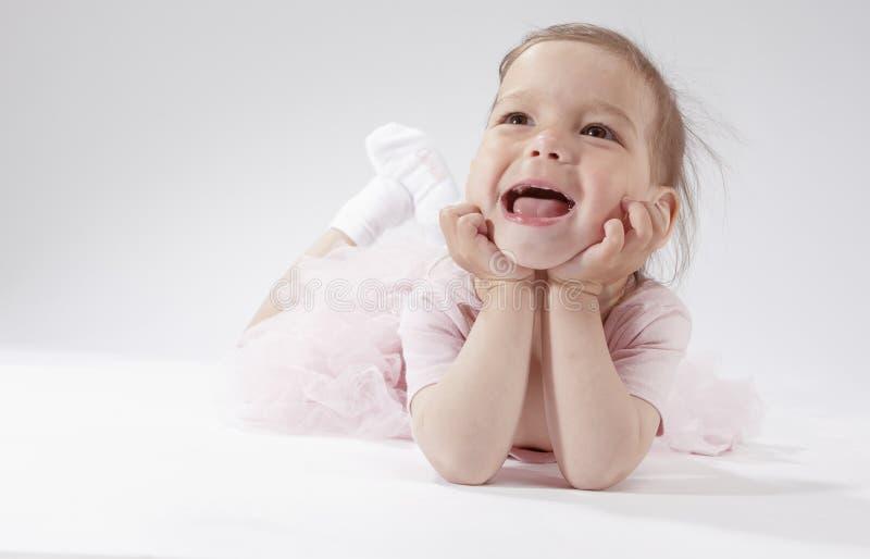 Lyckligt och le det lilla blonda barnet som poserar i rosa färgklänning mot vit bakgrund arkivfoto