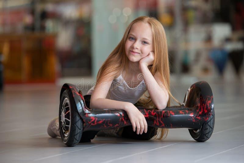 Lyckligt och le flickan med mini- segway på handelgallerian Tonåringridning på svävandebräde eller gyroscooter royaltyfri bild