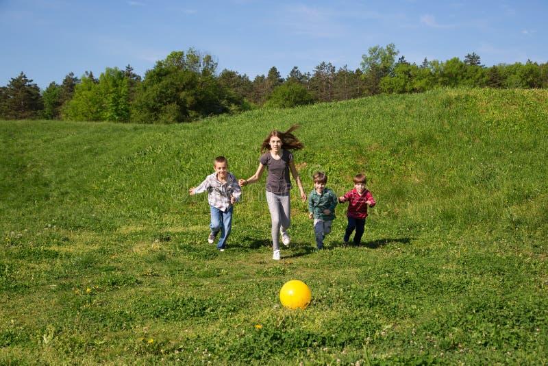 Lyckligt och le gruppen av ungar som kör till den gula bollen i det gröna fältet på Sunny Spring Day arkivbild