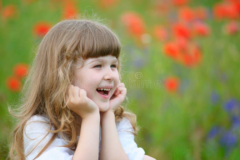Lyckligt och le liten flickaståendenärbild utomhus royaltyfri bild