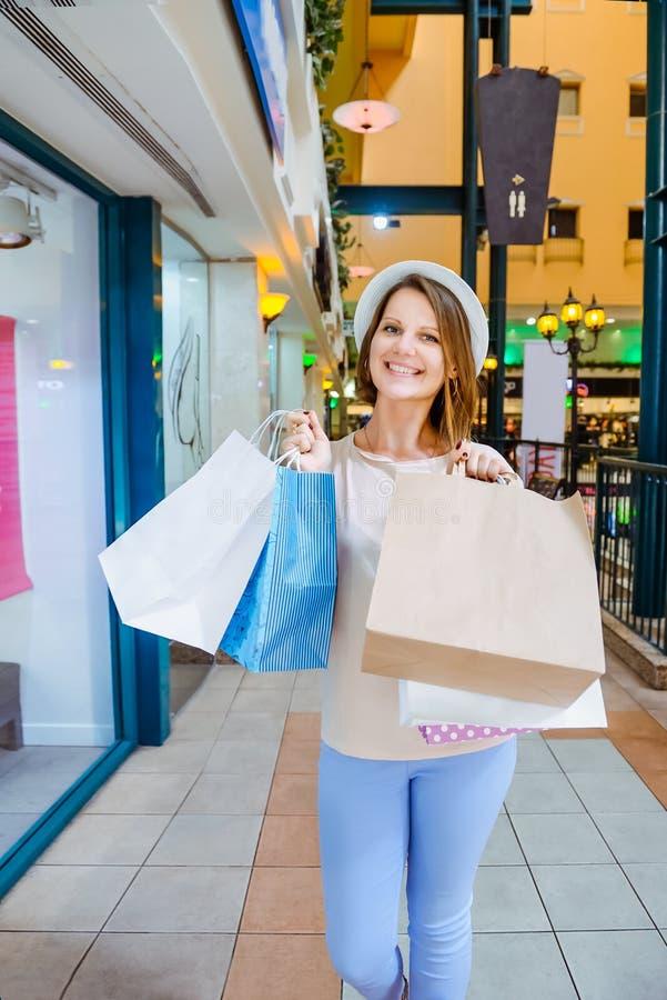 Lyckligt och le modeung flickaståenden Skönhetkvinna med pappers- påsar för hantverk i shoppinggalleria shoppare försäljningar Sh royaltyfri fotografi