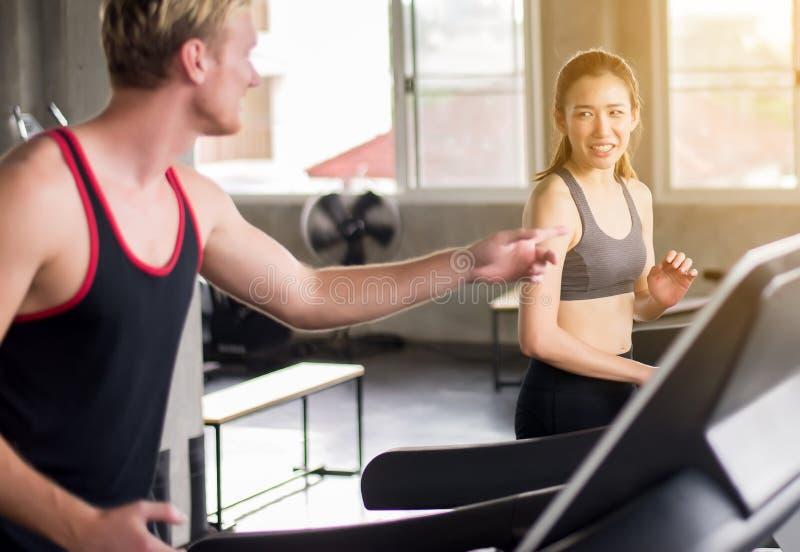 Lyckligt och le ung tonårig spring för par på trampkvarnar som tillsammans gör cardio utbildning i en idrottshall, sunt livsstilb royaltyfri bild
