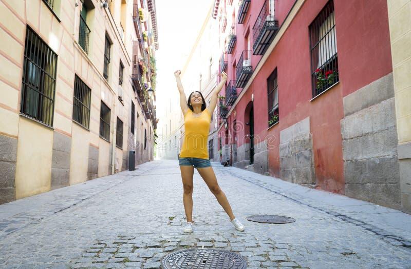 Lyckligt och upphetsat posera för ung attraktiv latinsk kvinna på modern stads- europeisk stad royaltyfria foton
