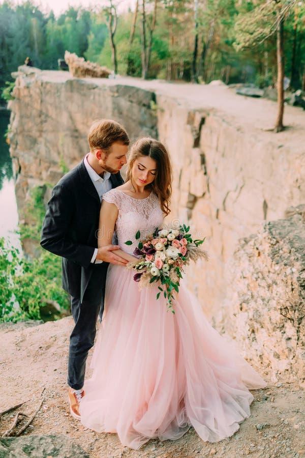 Lyckligt omfamna för nygifta personer Mannen i smoking och kvinna i en rosa bröllopsklänning poserar på naturen En ceremoni utomh royaltyfria foton
