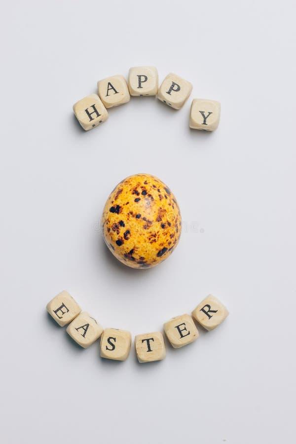 Lyckligt påskhälsningkort med träbokstäver och ägg arkivbild