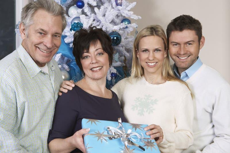 Lyckligt paranseende med gäster som rymmer gåvan arkivbilder