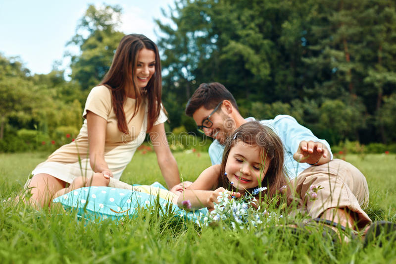 lyckligt parkbarn för familj Föräldrar och ungar som har gyckel som spelar royaltyfria foton
