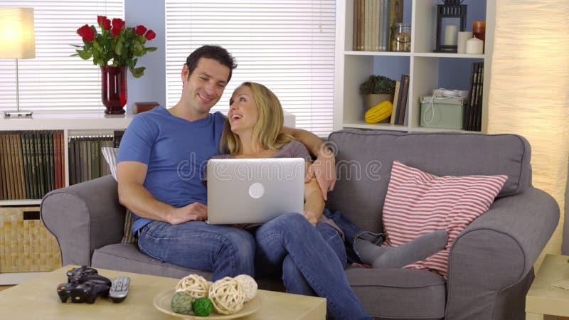 Lyckligt parsammanträde på soffan med bärbara datorn royaltyfri fotografi