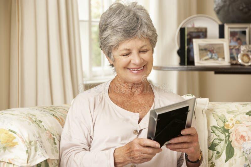 Lyckligt pensionerat högt kvinnasammanträde på det Sofa At Home Looking At fotografiet royaltyfria foton