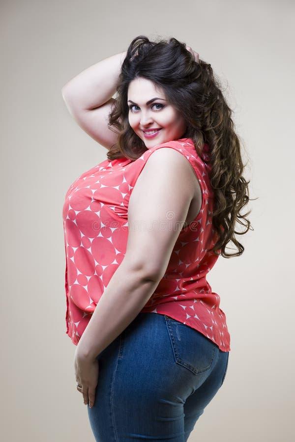 Lyckligt plus formatmodemodellen, sexig fet kvinna på beige bakgrund arkivbild