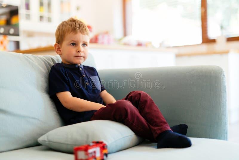 Lyckligt pojkesammanträde på vardagsrumsoffan royaltyfri foto