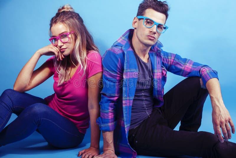 Lyckligt posera f?r par som tillsammans ?r gladlynt p? b?rande exponeringsglas f?r bl? bakgrund, grabb och v?nner f?r flickastude arkivbilder