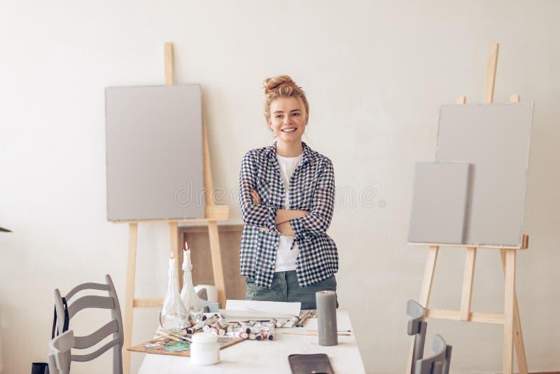Lyckligt positivt blont kvinnligt konstnäranseende med korsade armar royaltyfri foto