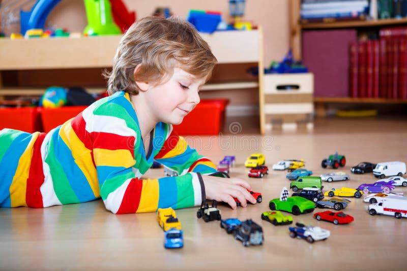 Lyckligt roligt litet blont barn som spelar med massor av leksakbilar arkivfoto