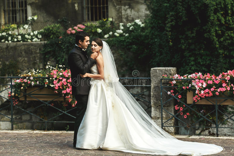Lyckligt romantiskt gift par som kramar på stenbron med flowe royaltyfri bild