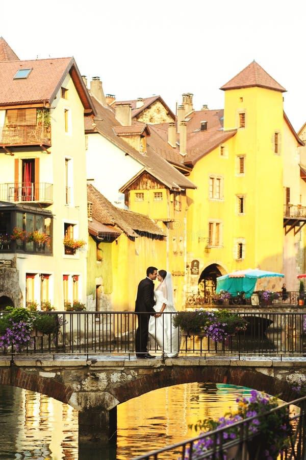 Lyckligt romantiskt gift par som kysser och kramar på den gamla bron arkivbilder