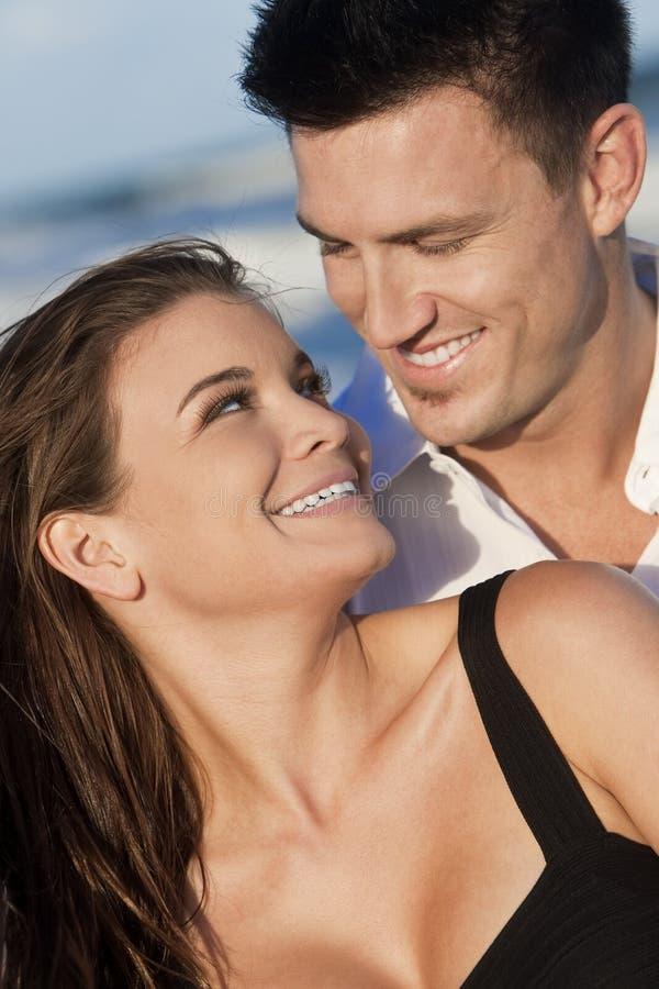 lyckligt romantiskt le för strandpar royaltyfria foton