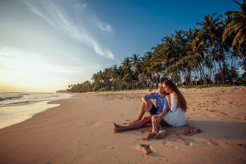 Lyckligt romantiskt parsammanträde på den tropiska stranden på palmträdbakgrund och att krama sig och tycker om solnedgång semest royaltyfri foto
