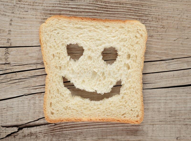 Lyckligt rostat bröd på ett gammalt trä royaltyfri foto