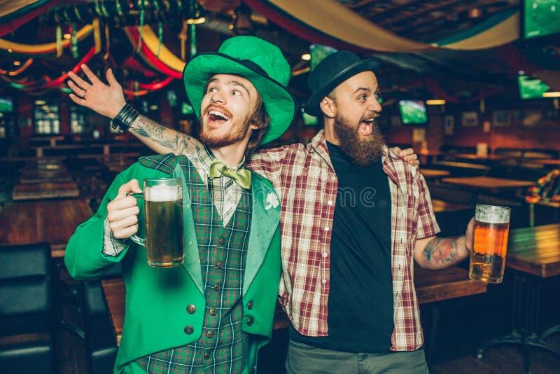 Lyckligt rymma för unga män rånar av öl och att sjunga tillsammans i bar De firar saitnpatricks dag Grabb på vänstra kläder royaltyfri fotografi