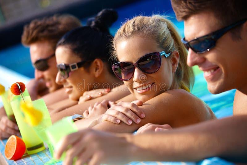 Lyckligt sällskap i vatten med coctailen arkivfoto