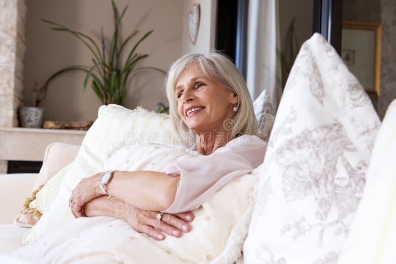 Lyckligt sammanträde för äldre kvinna på den kopplade av soffan royaltyfri fotografi