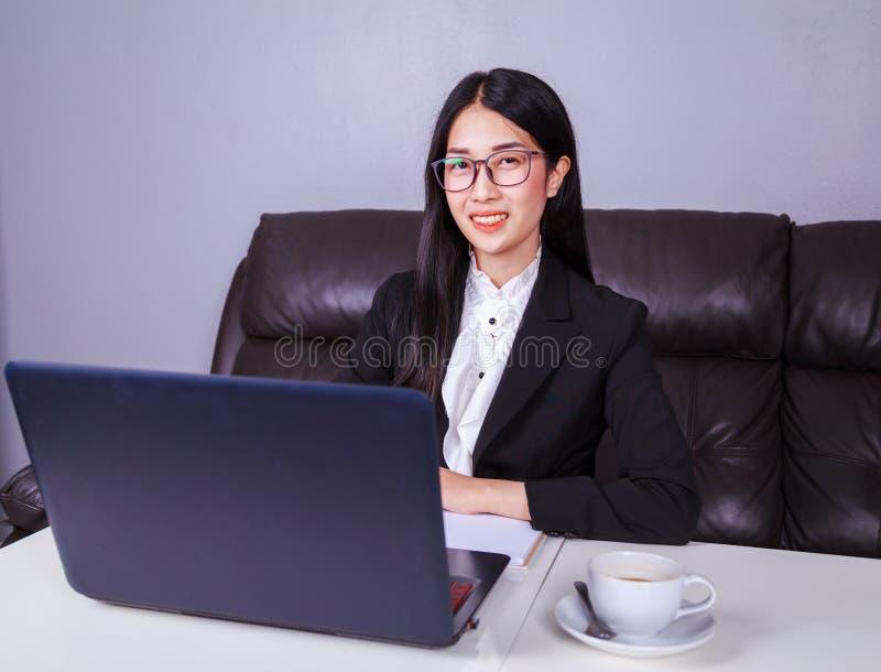Lyckligt sammanträde för affärskvinna på skrivbordet och använda bärbar datorcomput arkivfoto