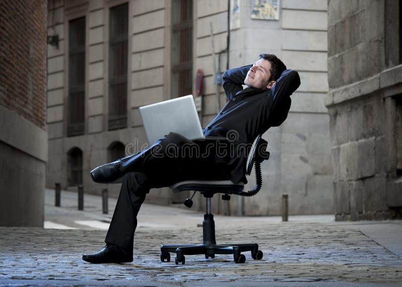 Lyckligt sammanträde för affärsman på kontorsstol på gatan med datoren arkivbild