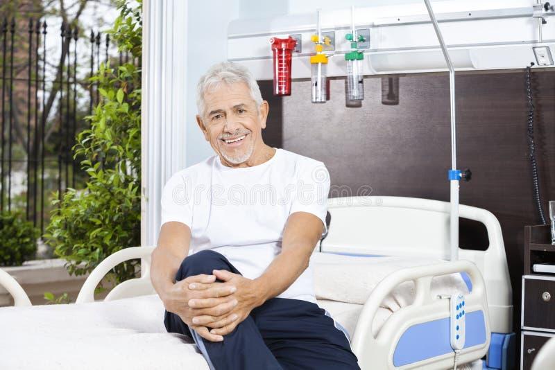 Lyckligt sammanträde för hög man på säng på rehabiliteringmitten royaltyfria foton
