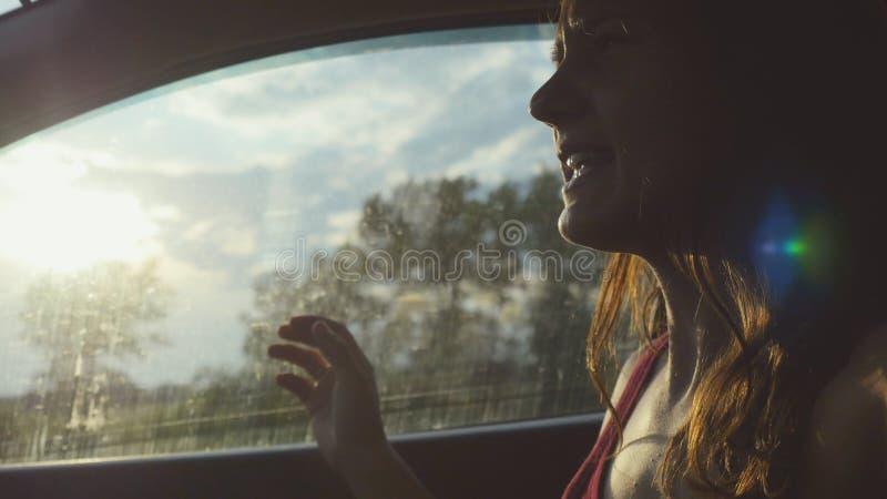 Lyckligt sammanträde för ung kvinna i bilpassageraren som ut ser fönstret på den soliga dagen som tycker om lantlig bilritt och s royaltyfri bild