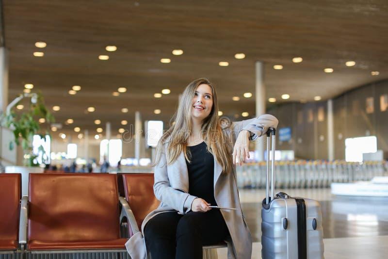 Lyckligt sammanträde för ung kvinna i väntande rum för flygplats med minnestavla- och grå färgvalise arkivbild
