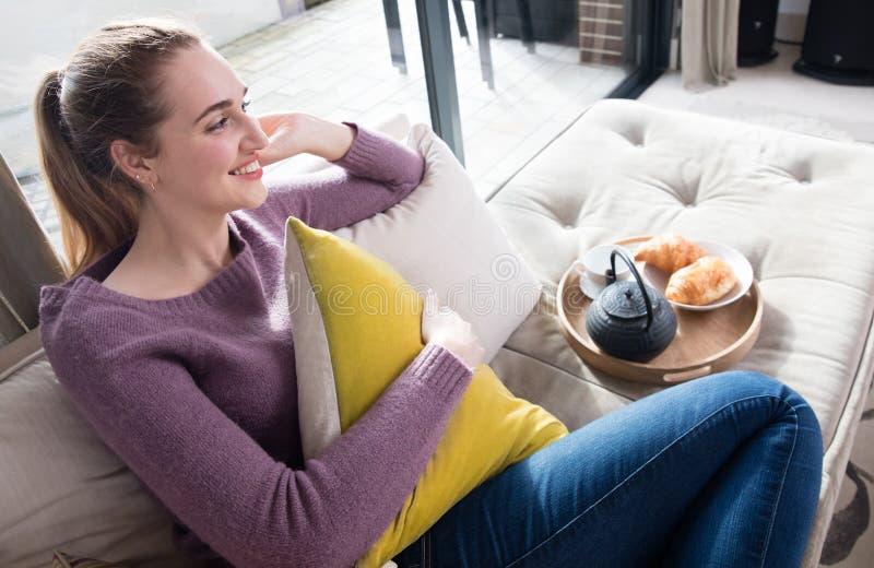 Lyckligt sammanträde för ung kvinna med den europeiska frukosten för avslappnande morgon royaltyfria bilder