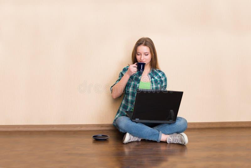 Lyckligt sammanträde för ung kvinna på golvet med korsade ben, genom att använda arkivbilder