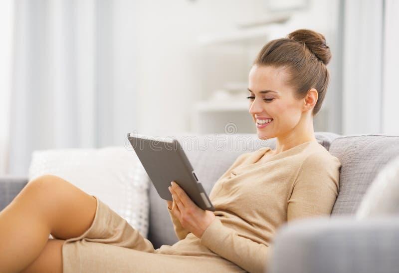 Lyckligt sammanträde för ung kvinna på soffan och arbete på minnestavlaPC royaltyfri fotografi