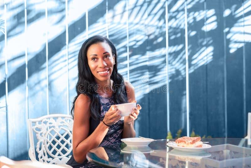 Lyckligt sammanträde för ung kvinna på tabellen i det utomhus- kafét royaltyfri bild