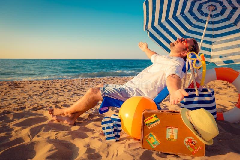 Lyckligt sammanträde för ung man på stranden royaltyfri bild