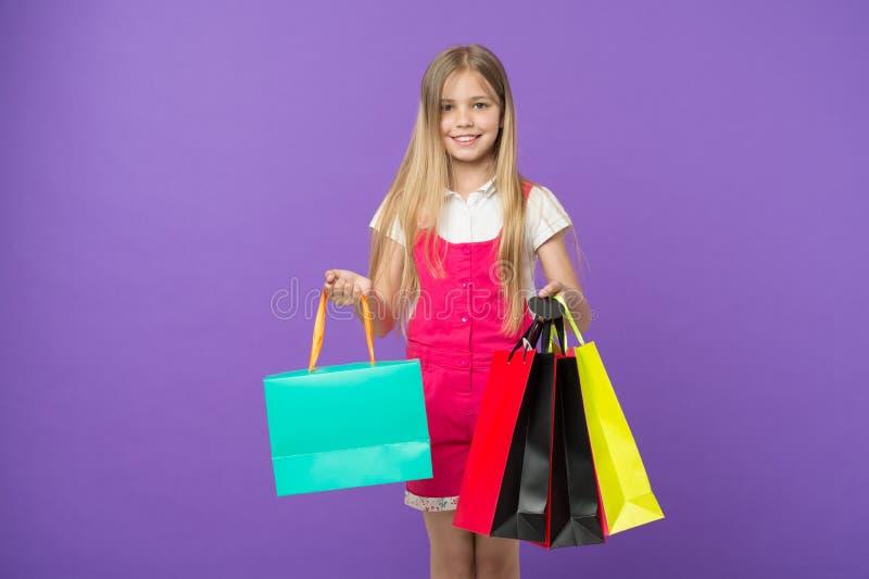 lyckligt shopaholic för flicka Barnköpobjekt på försäljningshåll samlar ihop påsar Flickan som ler den lyckliga framsidan, bär sh arkivbild