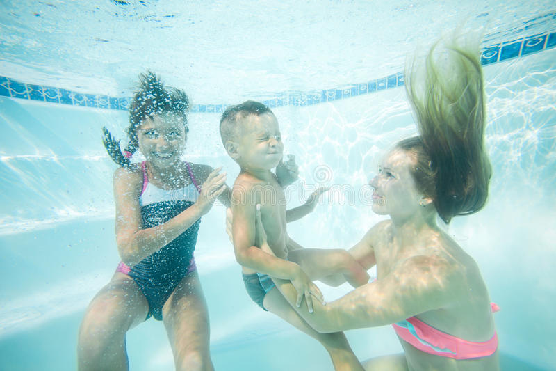 Lyckligt simma för familj som är undervattens- Moder, son och dotter som har att ha gyckel i pöl arkivfoton