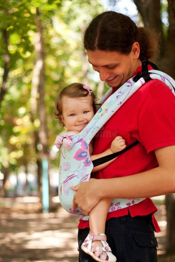Lyckligt sitta barnvakt i en bärande rem. arkivbilder