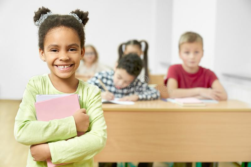 Lyckligt skolbarnanseende i klassrumet som rymmer böcker arkivbild