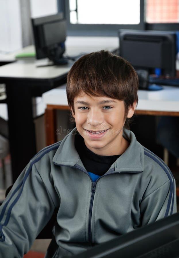 Lyckligt skolpojkesammanträde i datorgrupp royaltyfri fotografi