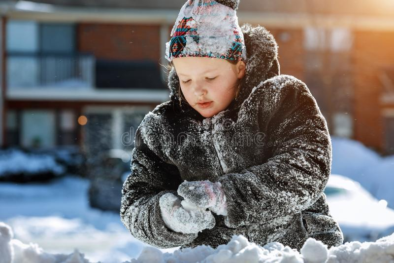 Lyckligt skratta bärande spela för liten flicka och att köra i en härlig snöig vinter parkerar mjuk skärpa, fokusungelek utanför royaltyfri foto